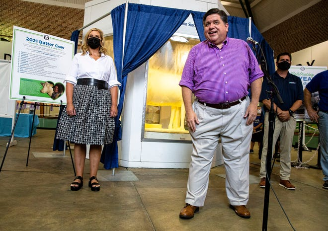 """Gov. JB Pritzker and first lady MK Pritzker unveil the 2021 Butter Cow, by sculptor Sarah Pratt, on Aug. 11 in the Dairy Building at the Illinois State Fairgrounds as they mark the 100th anniversary o the Butter Cow at the state fair. The theme of this year's Butter Cow is """"Embracing Tradition"""" and features a young exhibitor embracing the cow along with 13 hearts hidden throughout representing the 13 essential nutrients found naturally in milk. [Justin L. Fowler/The State Journal-Register]"""