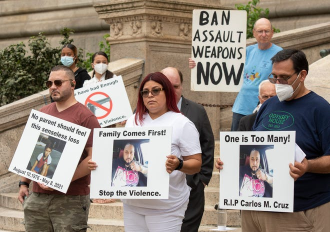 Family members of Carlos M. Cruz and others holds signs during an anti-gun violence rally in front of City Hall on Tuesday.