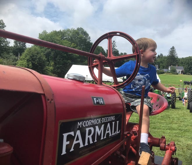 A youngster tries out an old Farmall tractor at the 2018 Hardwick Community Fair.