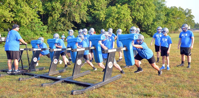 Williamsport assistant coach Anthony Cleary, left, stands on the blocking sled as players work on a drill during their first practice Wednesday.