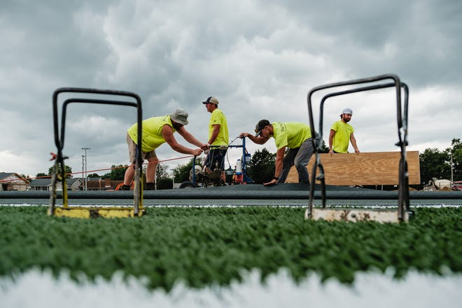 Tristan Reinhart (far left) and Brandon Milligan (third from left) sew together artificial turf panels at Claymont Stadium, Wednesday, Aug. 11. Also pictured are Rich Schoellman (middle) and Brendan Wilso (far right). Generally, it takes a crew from The Motz Group about three weeks to install an artificial turf field from start to finish — beginning with surveying, and ending when the surface is playable. Based in Cincinnati, the Motz group has recently completed projects such as Atlanta Braves Truist Park, Lucas Oil Stadium, and Cincinnati Bengals Paul Brown Stadium.