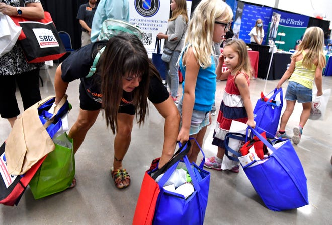 Alison Sargent, settles the bag her granddaughter Kaylen is carrying as her other two grandchildren, Railey in stripes and Kaylee in yellow, pull their bags of swag, or giveaways, during Wednesday's Business Expo at the Abilene Convention Center.