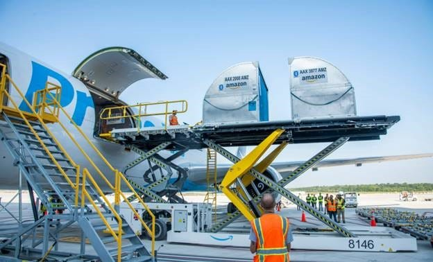 Amazon employees unload the very first packages off an Amazon plane at the new Amazon Air Hub at CVG.