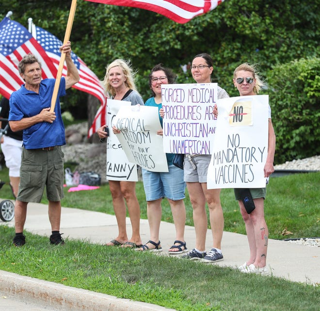 """A group of people gathered with signs Wednesday, August 11, 2021 outside St. Agnes Hospital in Fond du Lac, Wisconsin to protest the mandatory requirement for all hospital workers to get the COVID-19 vaccination. One woman's sign reads, """"Forced medical procedures are un-Christian and un-American."""""""