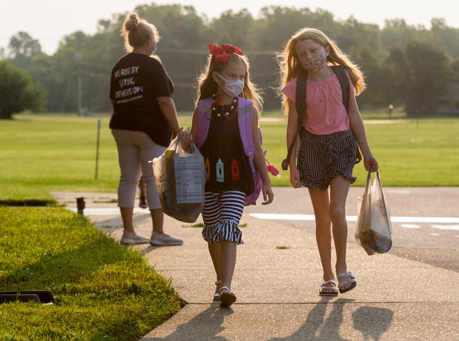Paisley Critser, left, and Paitlyn Critser, right, head to class after being dropped off on the first day of school at East Heights Elementary in Henderson County, Ky., Wednesday morning, Aug. 11, 2021.