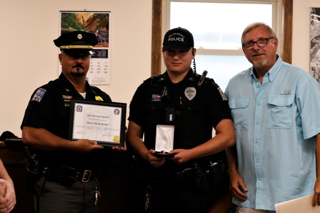 From left to right: Millersport Police Chief Mark Consolo, Officer Hiroki Barker and Mayor Gary Matheny. Barker was honored at the Aug. 11 village council meeting with a Life Saving Award and a Medal of Merit.
