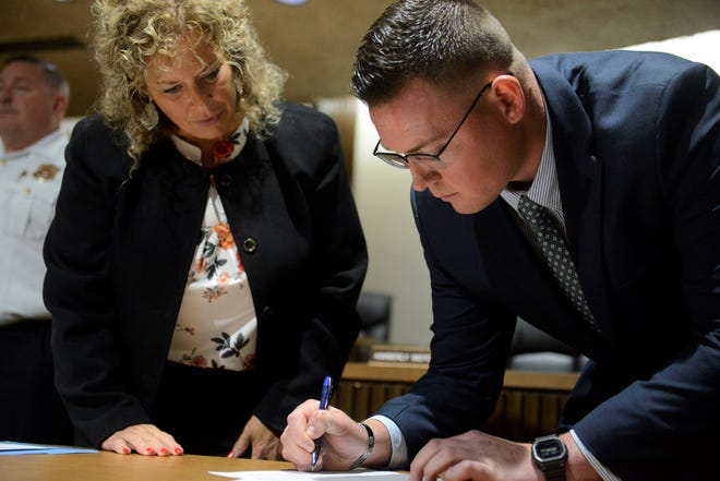 Ashton Bell signs the law enforcement oath of office as Safety-Service Director Lori Cope looks on.