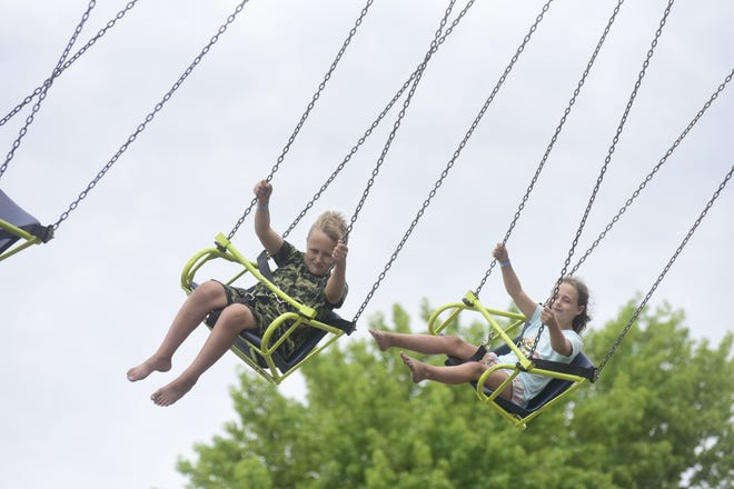 Izak Pelser, 10, and his sister, Ali, 8, of North Canton, ride the swings Wednesday morning during the 2021 the Richland County Fair.