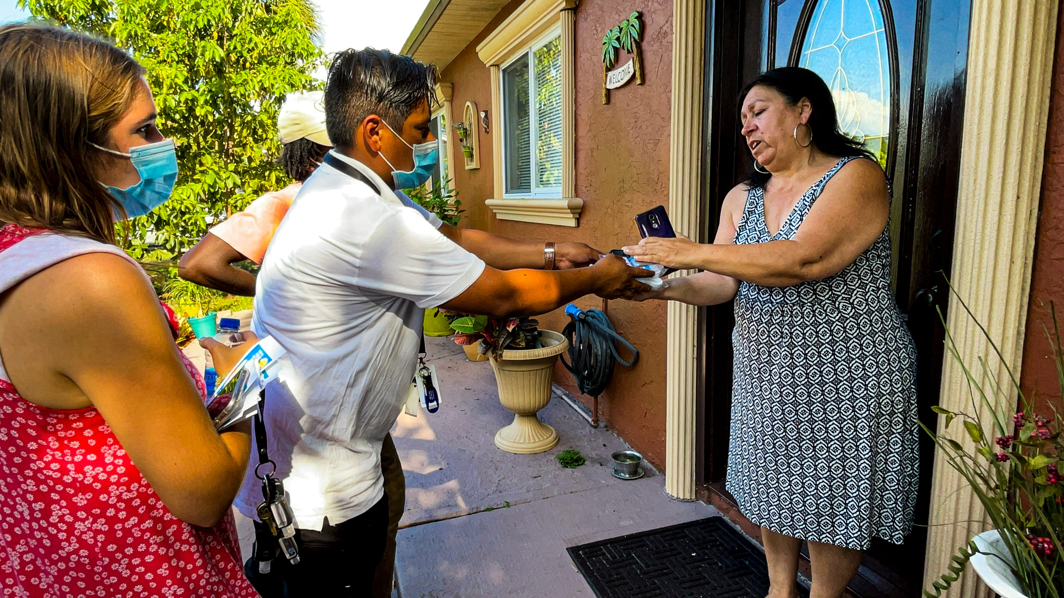 Healthcare Network worker Osman Lopez Hernandez hands a woman a packet of masks.