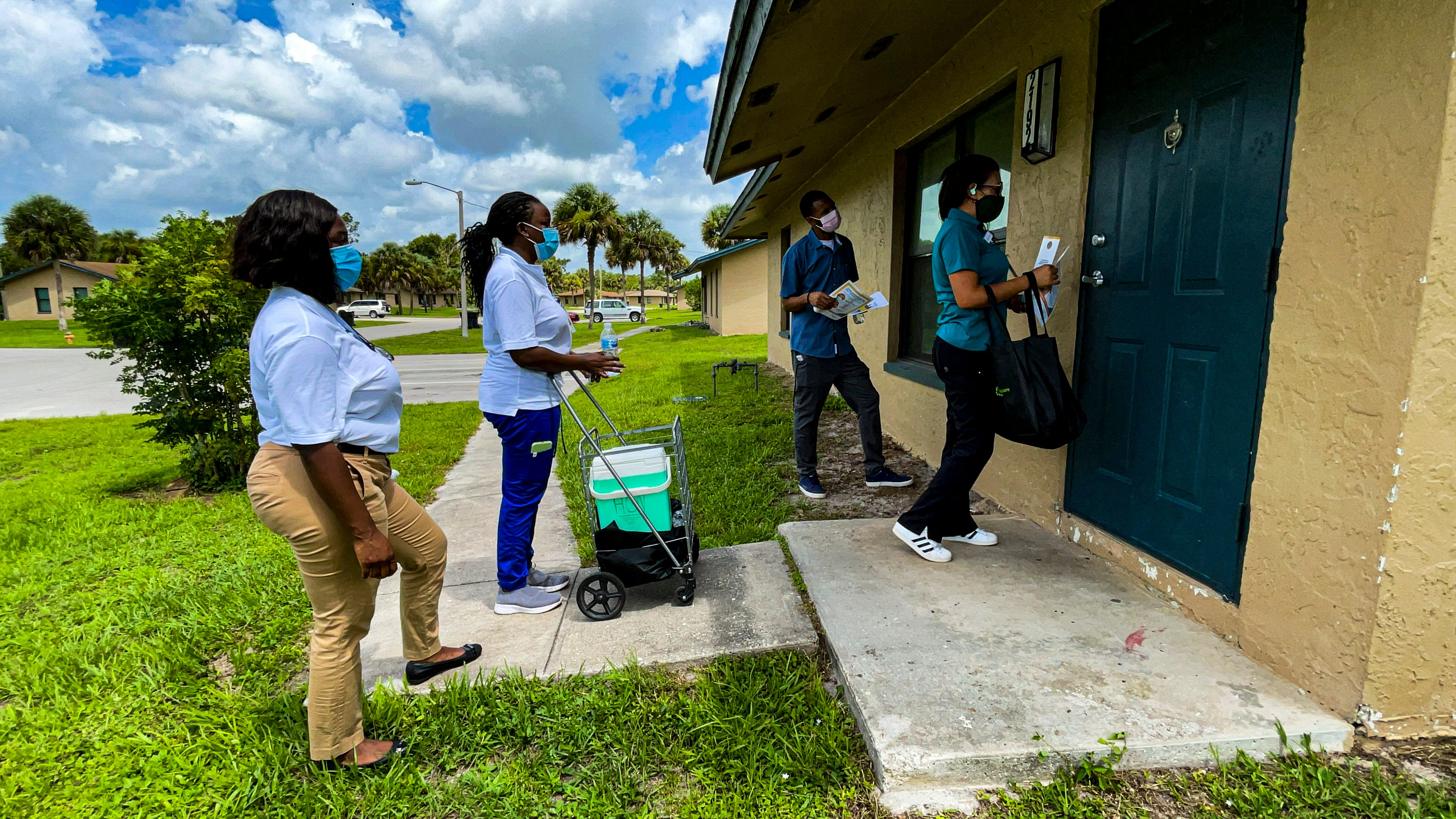 Healthcare Network COVID-19 response team members Junia Monpremier, Odilest Guerrier and Marisol Howell go door-to-door in July in Immokalee, Florida, offering information on vaccines and testing in a community known for its farmworker population.