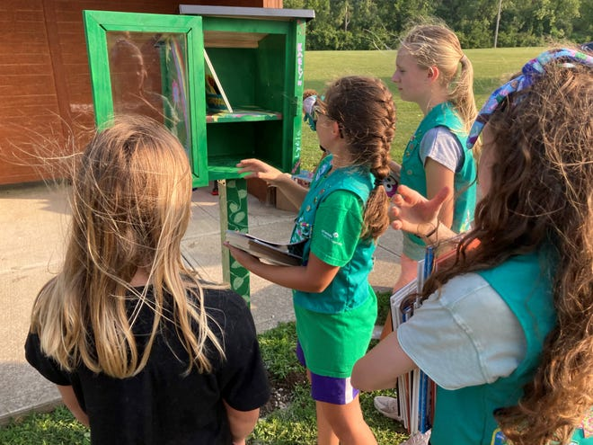 Members of Granville Girl Scout Troop 2907 stock their just completed little library in Raccoon Valley Park with books.