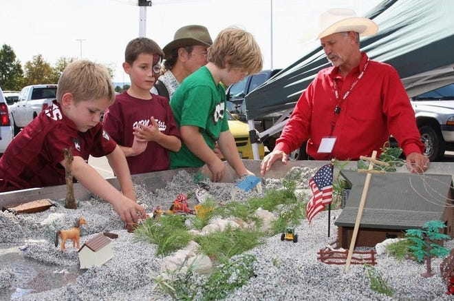 During a past AG Day event, children learn about water conservation as it relates to agriculture from Brent Van Dyke with the New Mexico Association of Conservation Districts as part of a hands-on, interactive activity. AG Day 2021 will take place on Saturday, Sept. 25 near Aggie Memorial Stadium ahead of the NMSU football homecoming game.