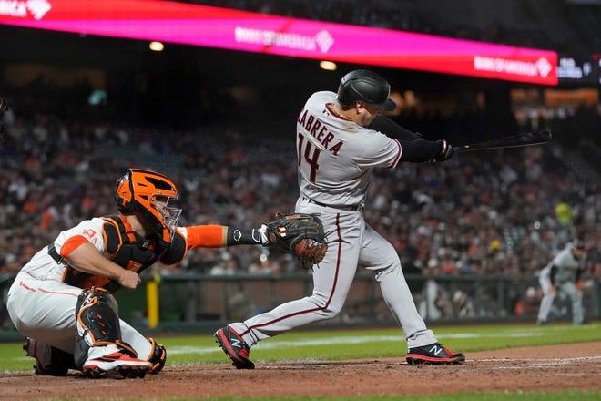 Arizona Diamondbacks' Asdrubal Cabrera (14) hits a two-run home run in front of San Francisco Giants catcher Buster Posey during the sixth inning of a baseball game in San Francisco, Tuesday, Aug. 10, 2021. (AP Photo/Jeff Chiu)