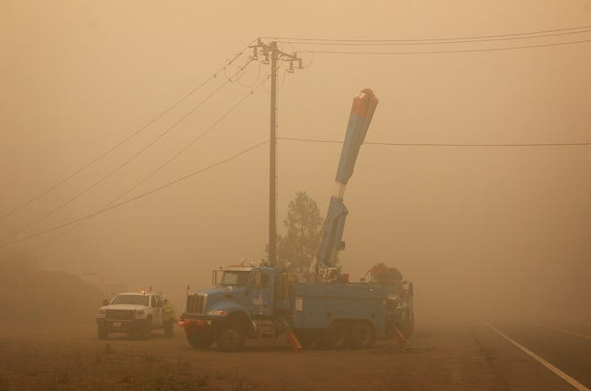 PG&E trucks and workers are seen along California Highway 89 near Greenville on Aug. 7, 2021.