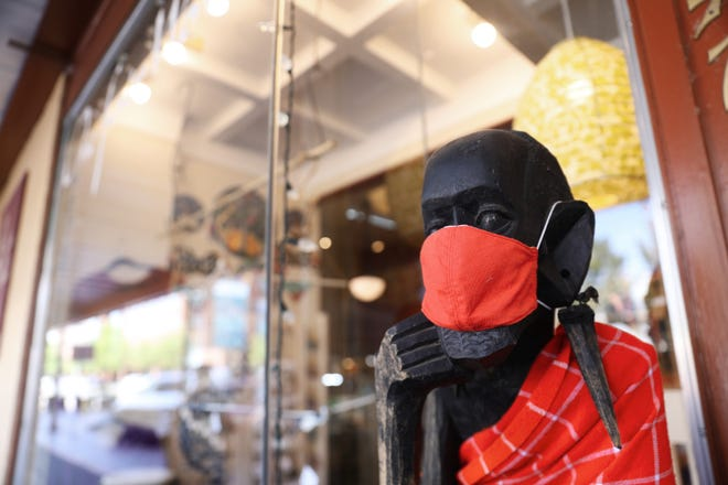 A figure wears a mask outside of One Fair World in downtown Salem.