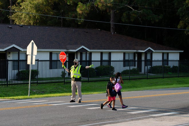 Students cross the street on the first day of school at Oak Ridge Elementary School Wednesday, August 11, 2021.