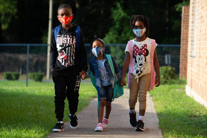 Three students walk hand and hand into school on the first day at Oak Ridge Elementary School Wednesday, August 11, 2021.