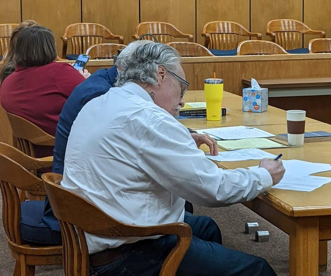 James Lynn Mazy signs court documents after hearing a punishment verdict Wednesday for his conviction of two counts of injury to an elderly person in 89th District Court.