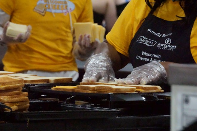A volunteer assembles grilled cheese sandwiches on the griddle.