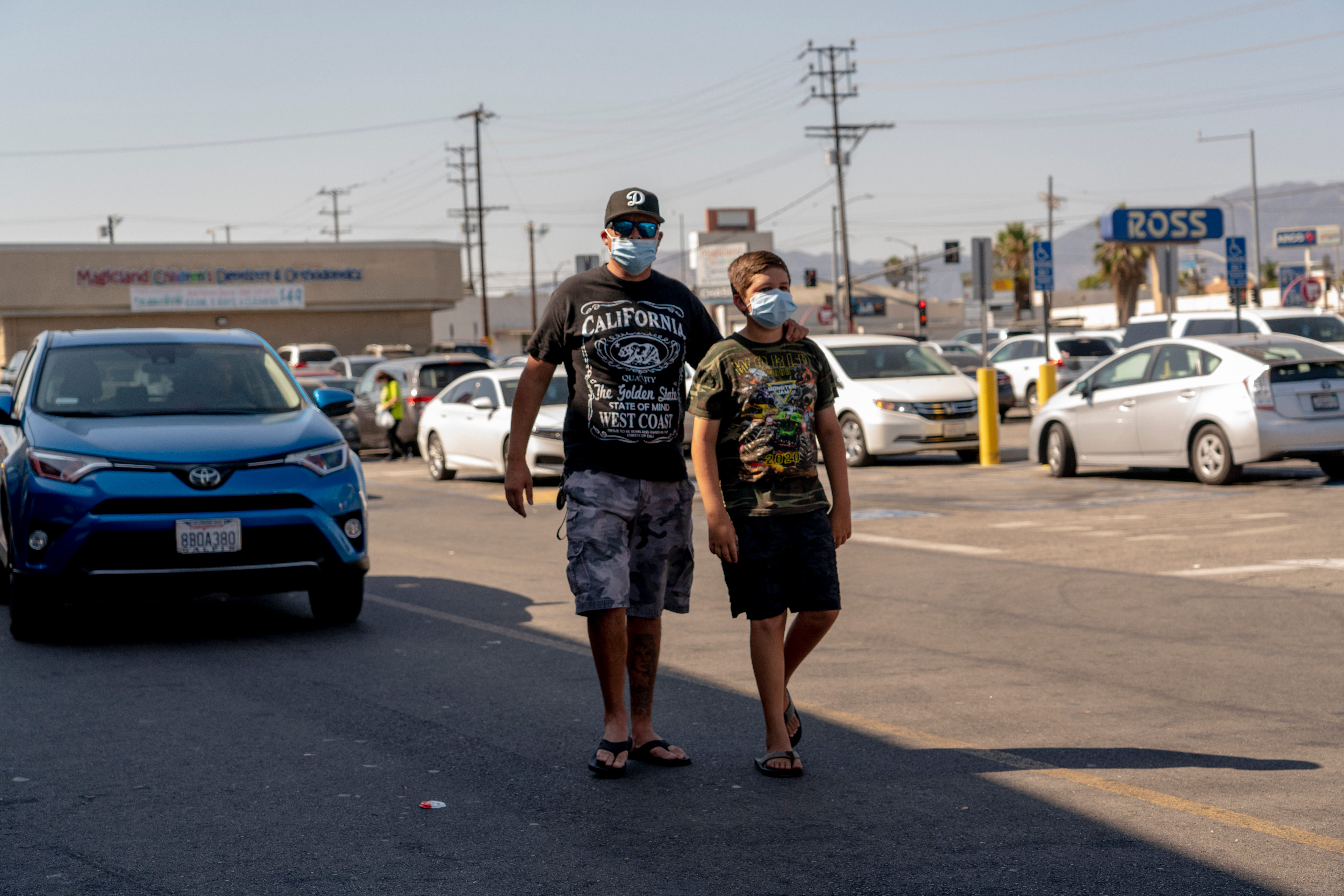Joel Reynozo, left, walks with his son, Jared, 11, after leaving a Target store in Pacoima last week. Reynozo, who is unvaccinated, says he would pull his son out of Los Angeles Unified if the district requires students to be vaccinated.