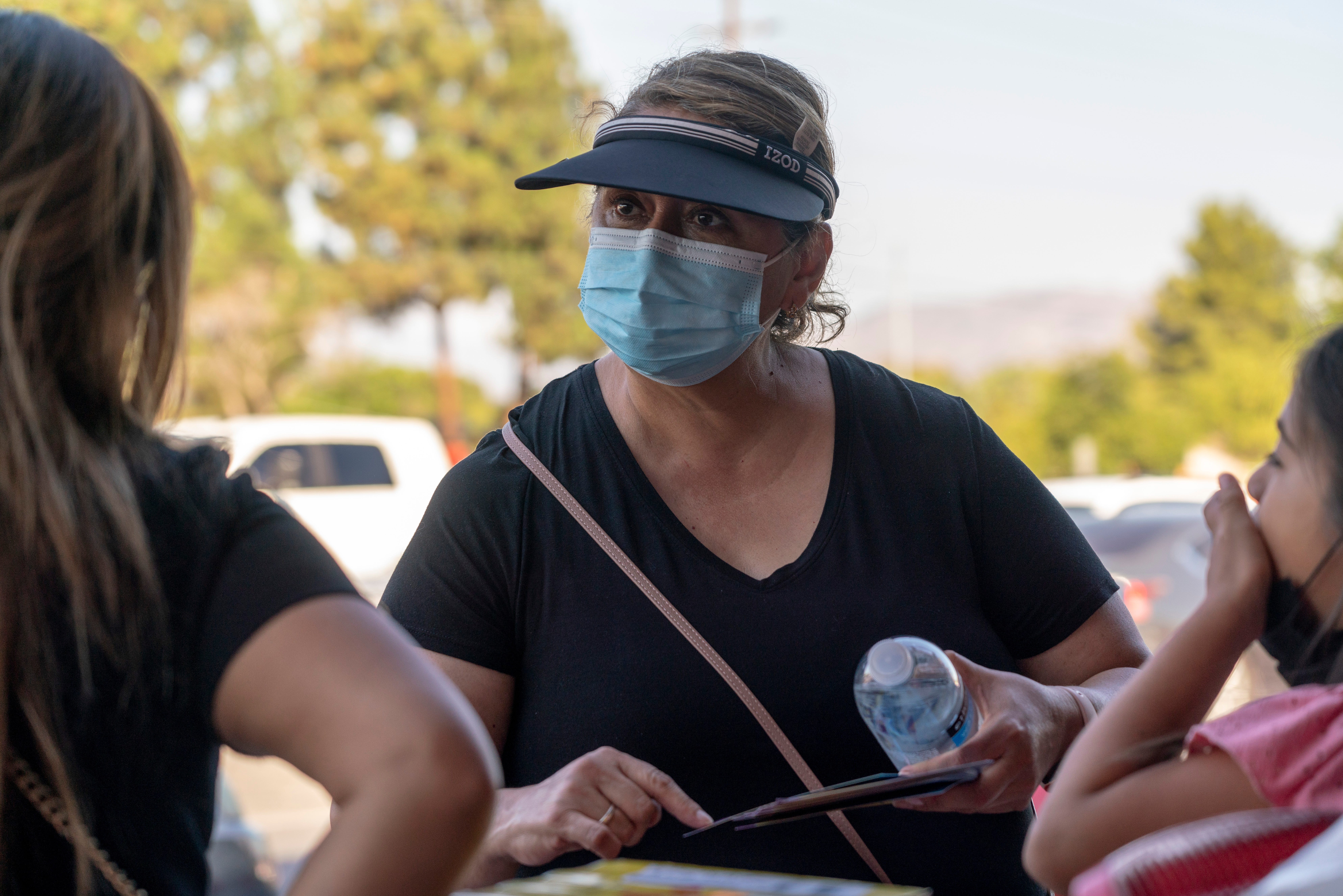 Hilda Martinez, a community organizer with the L.A. Education Recovery Fund hands out informational flyers about the Los Angeles Unified School District's requirements for students to return to in-person classes outside a Target store in Pacoima, Calif., Aug. 10, 2021.