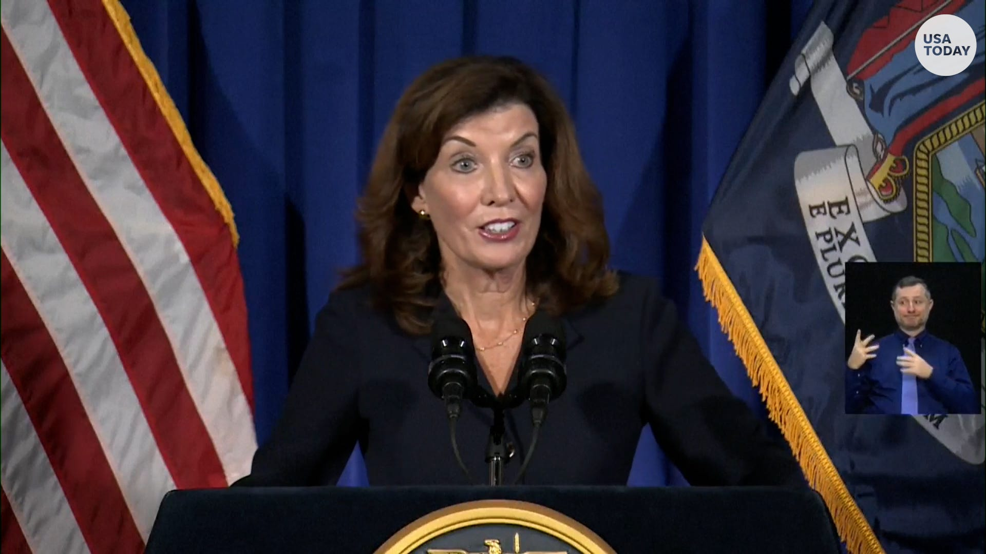 New York Lt. Gov. Kathy Hochul raises her arms as she stands behind a podium.
