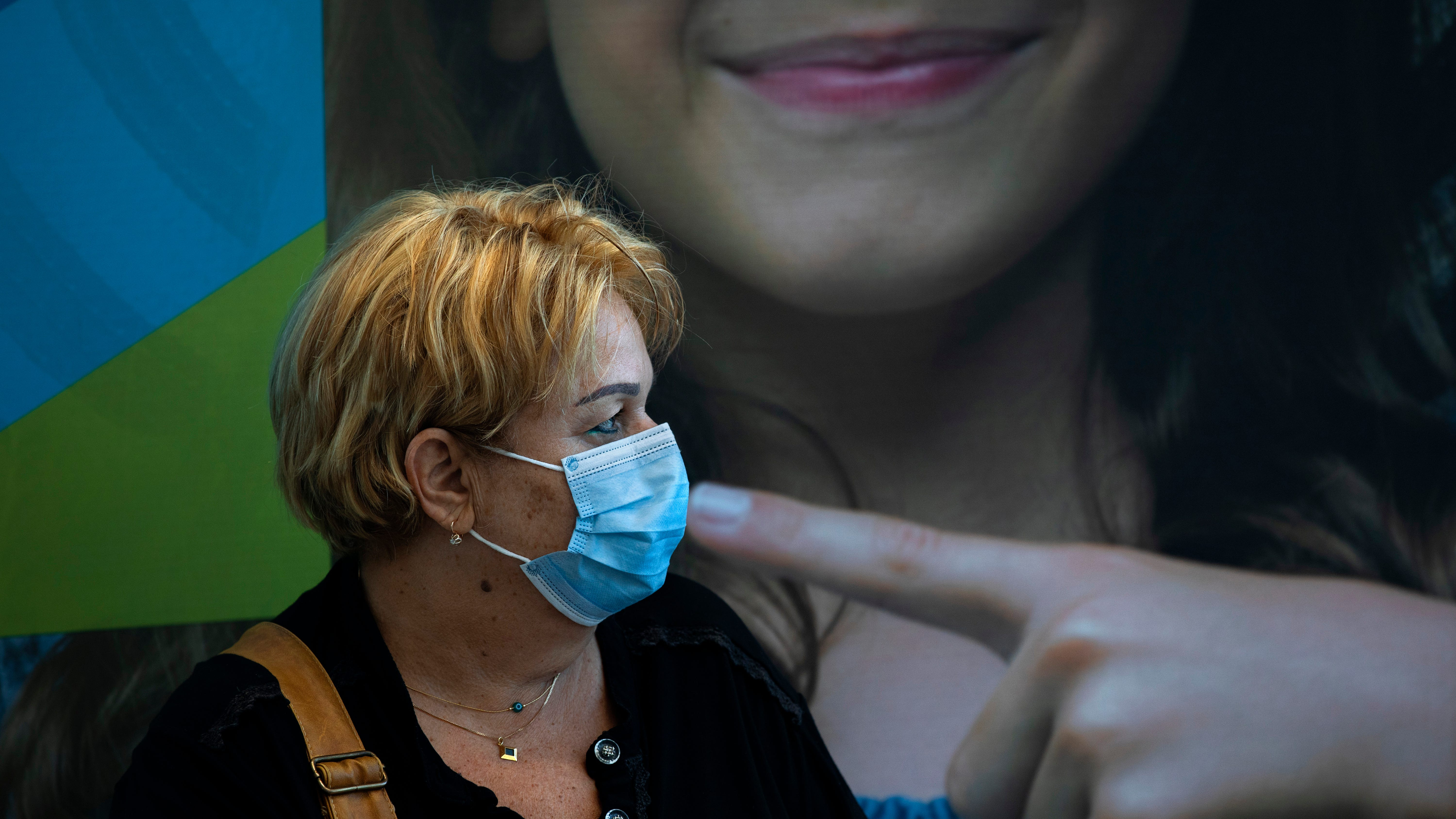 A woman rests after receiving a third Pfizer-BioNTech COVID-19 vaccine at a coronavirus vaccination center in Tel Aviv, Israel, Tuesday, Aug. 10, 2021. Israel is grappling with a surge of infections and urging people over age 60 to get a booster shot.