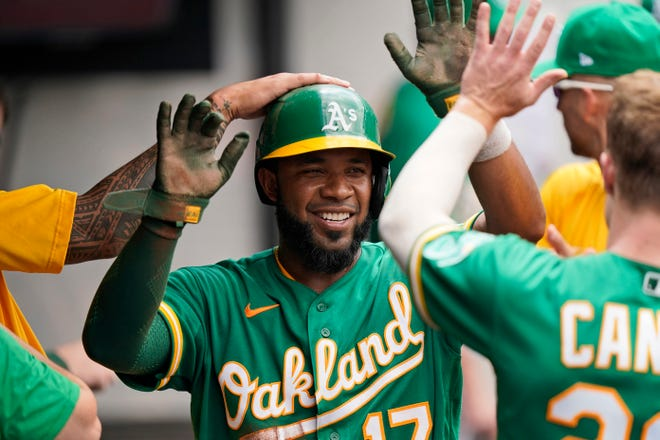 The Oakland Athletics' Elvis Andrus is congratulated by teammates after scoring in the fourth inning of a 17-0 win over Cleveland on Thursday afternoon at Progressive Field. [Tony Dejak/Associated Press]