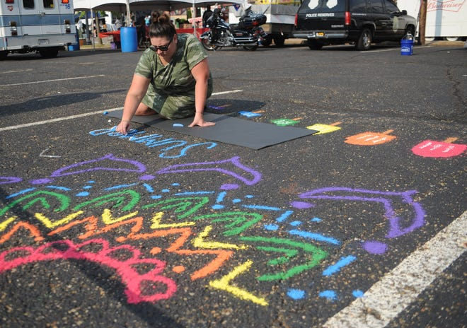 """Kayla Johnson works on her chalk entry """"Summer Yum"""" during the Greater Alliance Carnation Festival Chalkfest on Saturday, Aug. 7, 2021, in downtown Alliance."""