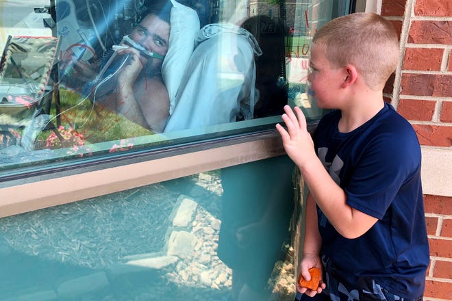 Brody Barker waves to his father, Daryl, from outside his hospital room in Osage Beach on July 26 as he recovers from COVID-19. The death toll from COVID-19 in Missouri has now topped 10,000. The state health department's coronavirus dashboard on Thursday showed 20 new deaths.