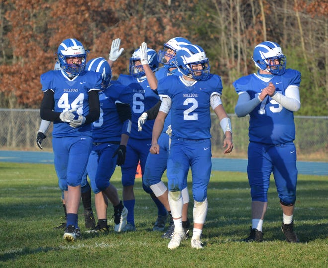 Quarterback Mason Blumke (2) and Inland Lakes football players celebrate a playoff victory over Munising in Indian River last season. The Bulldogs are coming off an 8-2 campaign that featured three postseason wins and a first-ever regional title for the program.