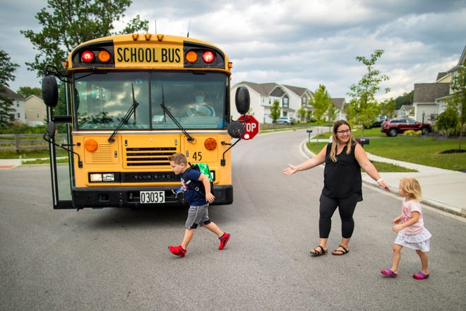 Aiden O'Grady, 6, runs to hop on the school bus for his first day of first grade at Hanby Elementary in Westerville as his mom, Kim, and sister, Abby, cross the street of their Minerva Park neighborhood on Thursday. After attending kindergarten virtually, Aiden couldn't wait to meet his classmates in person this school year.