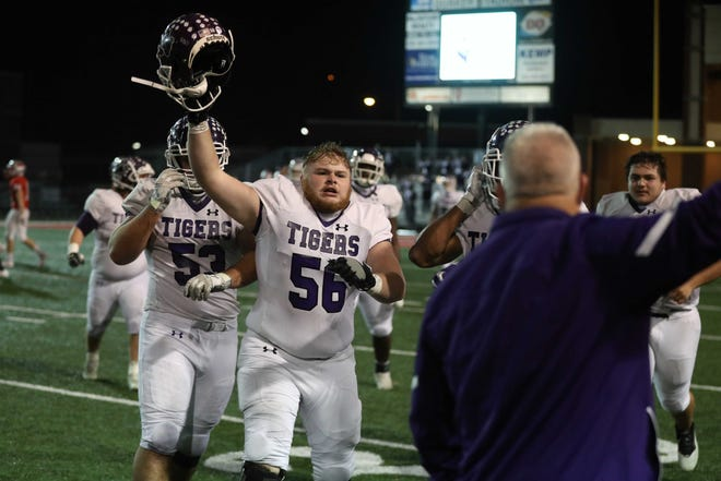 Pickerington Central lineman Brock Egan (56) leads a parade of teammates to celebrate the Tigers' 38-31 victory over Mentor in a 2020 Division I state semifinal.