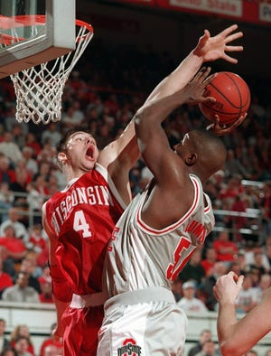 John Lumpkin, here shooting against Wisconsin's Sam Okey, lettered in football from 1996-98 and played basketball for four years.
