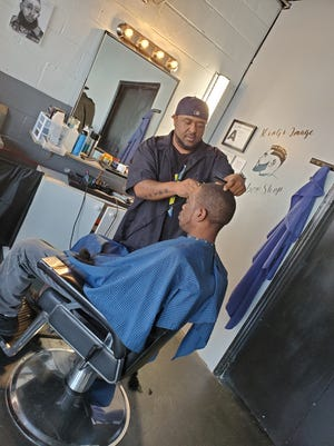 Adrian Carthens, owner of Kings Image Barber Shop, opened his business on Aug. 7. The Lexington native works on David Cuthrell's hair in this photo. He also opened  Maximum Auto Detail on Aug. 14 behind the barber shop to offer residents a place to get their car cleaned while they get their hair cut.