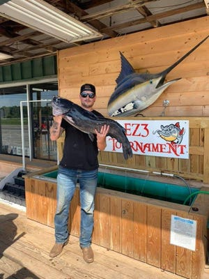 Taner Rudolph, a Marine Corps veteran from Hubert, holds up his state record 26-pound channel catfish caught in the Neuse River near Kinston in July.