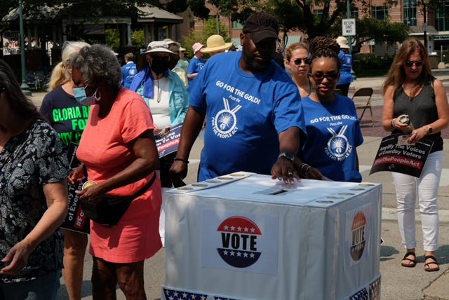 Pastor Terrence Johnson of Second Missionary Baptist Church casts a ballot during a symbolic vote at a rally to support For the People Act in downtown Monroe recently.