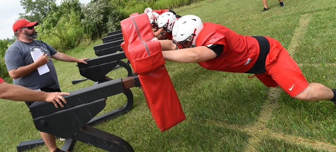 Monroe High School lineman coach Kyle Reed blows the whistle as the lineman hit and push the sled on the first day of pads this past week.