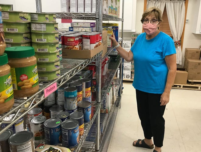 Hamilton Food Cupboard director Suzanne Collins poses Aug. 12 with some of the items available for the needy at the community pantry's new location on Airport Road. The food cupboard is open from 1-6 p.m. Tuesdays and Thursdays.