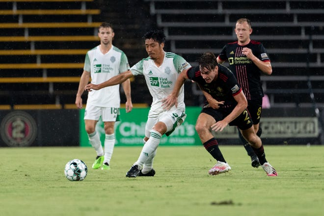 Oklahoma City's Hiroki Kurimoto, left, races an Atlanta player to the ball during Wednesday's United Soccer League match in Kennesaw, Ga. The game finished in a 2-2 draw.
