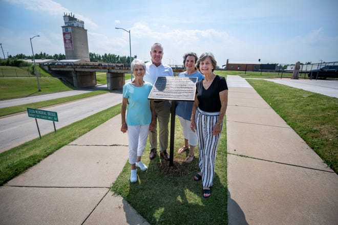 Steen family descendants pose with the plaque designed by Judy Pike, of the Edmond Historic Preservation Trust. Shown left to right are Charlene Zielinski, Dr. Steve Zielinski, Debra Zielinski Coller and Virginia Sparks. The Steen Memorial Bridge, a bridge of the Burlington Northern Santa Fe Railway, can be seen in the background in downtown Edmond.