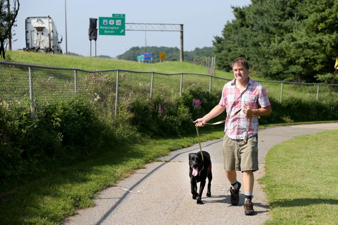 Portsmouth resident Justin Richardson walks his dog, Milo, along a bike path near his house parallel to the highway on Thursday morning.
