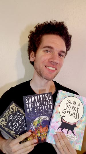 Author, poet and visual graphic artist Sage Liskey with a few of his many books and 'zines designed to deliver positive, reinforcing mental health.