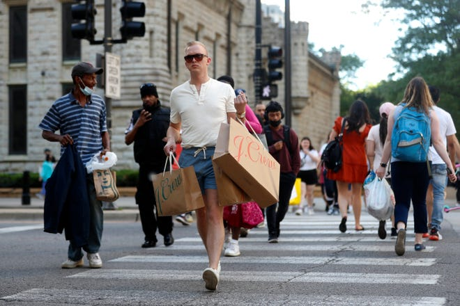 Troy Hemlin, shown visiting Chicago from Springfield on May 26, 2021, crosses the street in downtown Chicago. The latest census data shows Illinois again lost population, although Chicago remains the third-largest city in the nation.