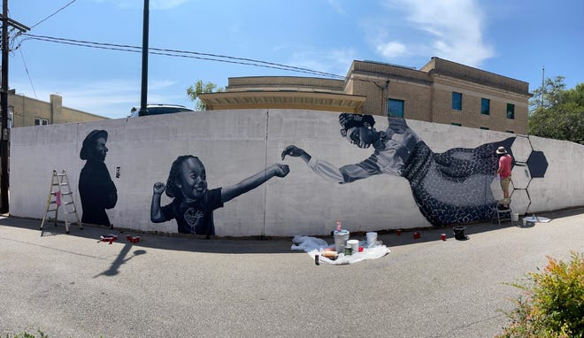 Casey Quinn works on the Sankofa mural outside the Cleveland County Arts Council building.