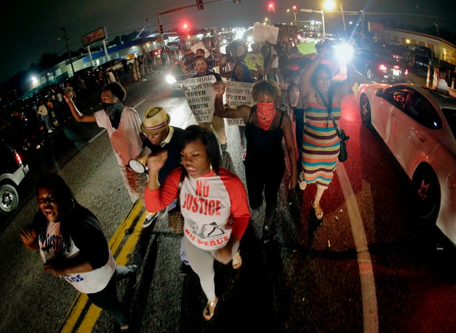 In this Friday, Aug. 15, 2014 photo, protesters march down the middle of a street in front of a convenience store in Ferguson, Missouri, that was looted and burned following the shooting death of Michael Brown, an unarmed black teenager, by a white police officer on Saturday, Aug. 9, 2014. Demonstrators were demanding justice for the 18-year-old Brown.
