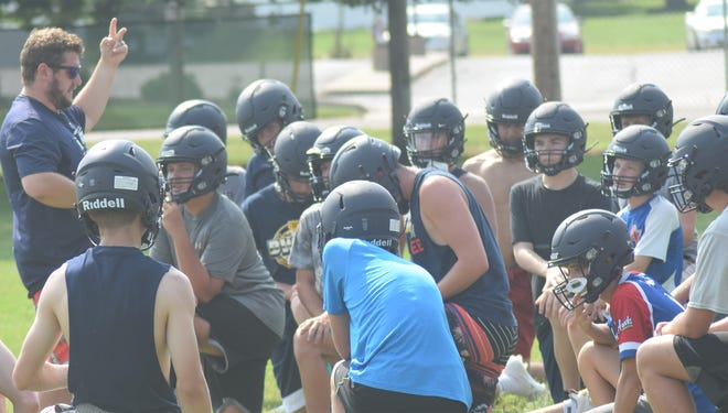 New Annawan-Wethersfield football coach gathers his team around for a talk during the first week of practice earlier this week. The Titans will host Monmouth United in the first game of the season Friday, Aug. 27.