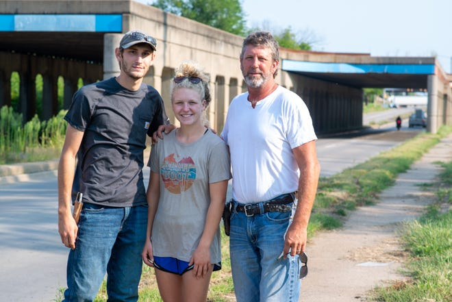 Russell Torrey, right, co-owner of Wamego-based Torrey Bros Inc., stands alongside his daughter Ashton Torrey, and company foreman Clay Patterson, outside of South Topeka Boulevard on Monday morning. Torrey volunteered his equipment to sandblast sections of the railroad bridge in the background.