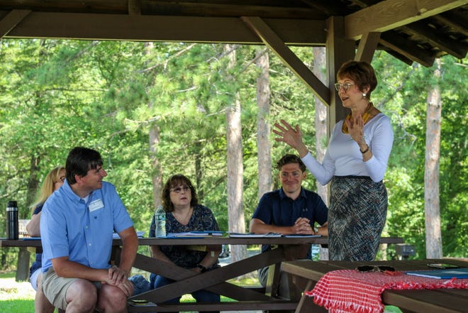 Huddling with local officials at Mount Sugarloaf State Reservation in South Deerfield, State Auditor Suzanne Bump, right, discussed the findings of her office's report on PILOT reimbursements.