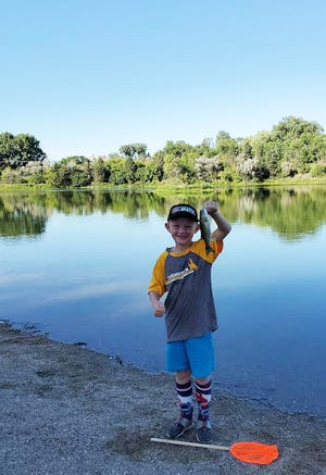 Brody Poppen caught a fish with the help of his grandpa Tom Morteson Wednesday evening at Riverside Park in Watertown.